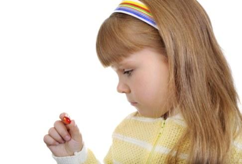 Fetita cu pastila in mana