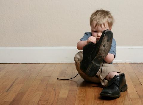 copil care incearca sa se incalte