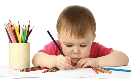 Copil ce scrie cu creioane colorate