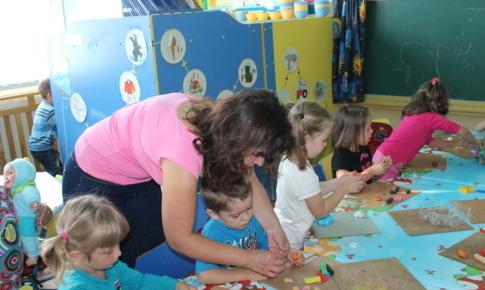 Doamna educatoare le arata copiilor cum sa faca figurine din plastilina