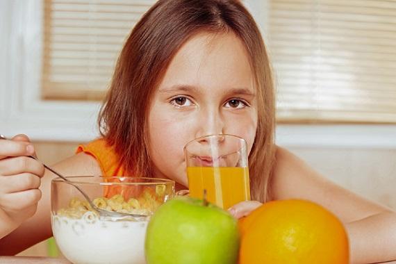 Fetita ce mananca lapte cu cereale si bea suc de portocale