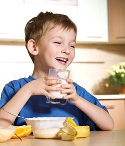 Copil ce bea lapte si are alaturi si banana