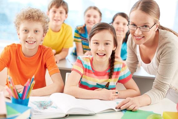 Copii veseli in clasa, alaturi de profesoara lor