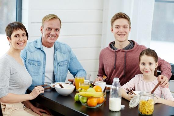 Familie formata din parinti si doi copii, la micul dejun