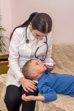 Medic care ii administreaza spray nazal unui baietel
