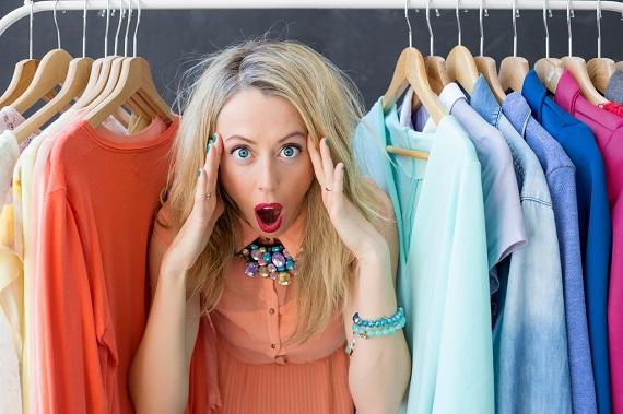 Femeie care se uita ingrozita la hainele din sifonier