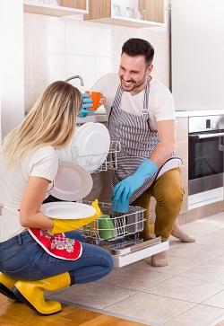 Cuplu ocupandu-se de vasele din masina de spalat vase
