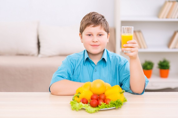 Copil ce are in fata sa o farfurie cu fructe si legume