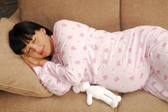 Tanara insarcinata ce doarme pe canapea
