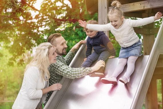 Copii fericiti, ce se dau pe topogan