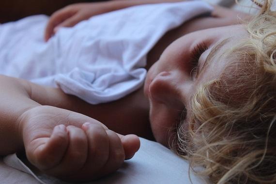 Baietel blond, care doarme invelit cu un cearceaf alb
