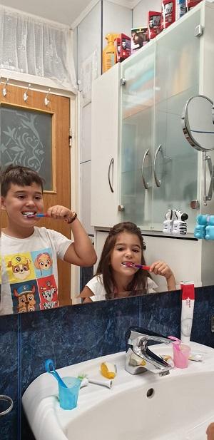 Fetita si baiat care se spala pe dinti in fata oglinzii