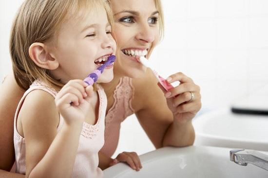 Mama si fiica, spalandu-se pe dinti impreuna