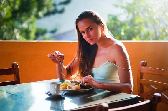 Tanara care ia micul dejun pe terasa