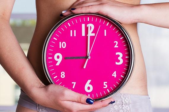 Femeie ce tine un ceas in dreptul abdomenului sau