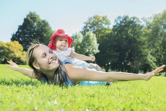 Mama face exercitii fizice in mijlocul naturii cu bebelusul ei