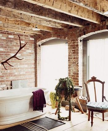 Baie rustica, cu grinzi, cu scaunel cu trei picioare si coane de cerb