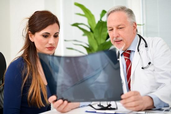 Femeie ce se uita la o radiografie impreuna cu medicul