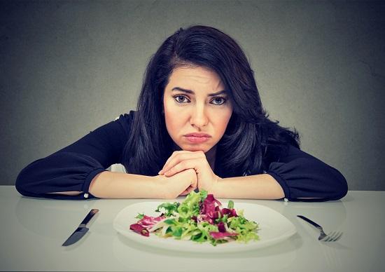 Femeie ce sta trista in fata unei farfurii cu salata