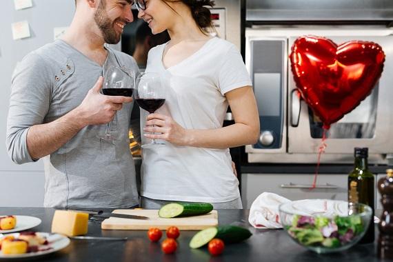 Cuplu in bucatarie, ciocnind cate un pahar de vin