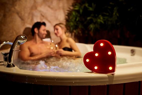 Cuplu ce face baie,ciocnind si cate un pahar de vin