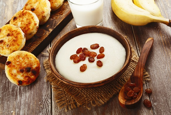 Griș cu lapte, alături de un pahar de lapte, banană și un alt preparat