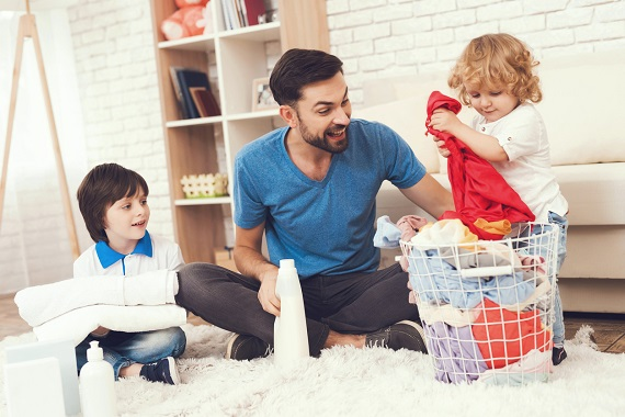 Tata alaturi de cei doi copii, ajutandu-se de ei pentru a pune lucruri in masina de spalat
