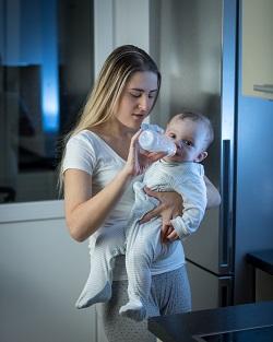 Mama ce isi tine bebelusul in brate, in pozitie verticala, ca sa ii dea lapte cu biberonul