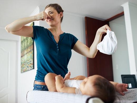 Mama care isi astupa nasul dupa ce a schimbat scutecul bebelusului