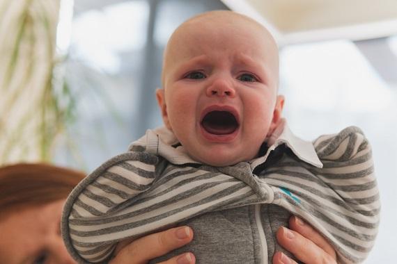 Bebelus rosu la fata, care plange