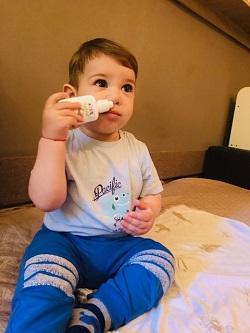 Bebelus care incearca sa-si puna picaturi in nas
