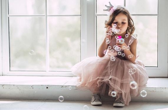 Fetita imbracata in  printesa, care face baloane de sapun
