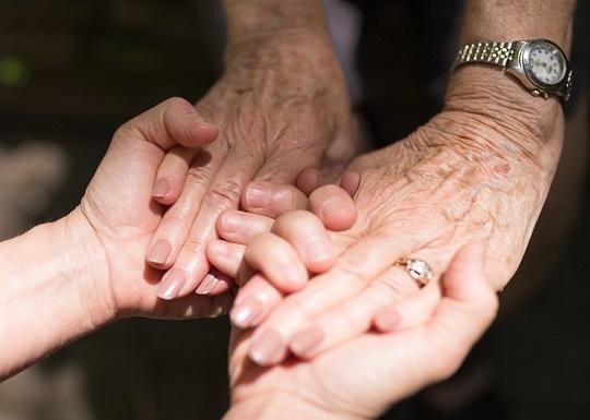 Mainile unei persoane varstnice tinute de mainile unei persoane tinere