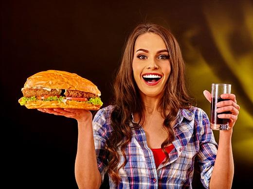 Femeie ce tine intr-o mana un hamburger urias si in cealalta un pahar de suc ce nu este natural