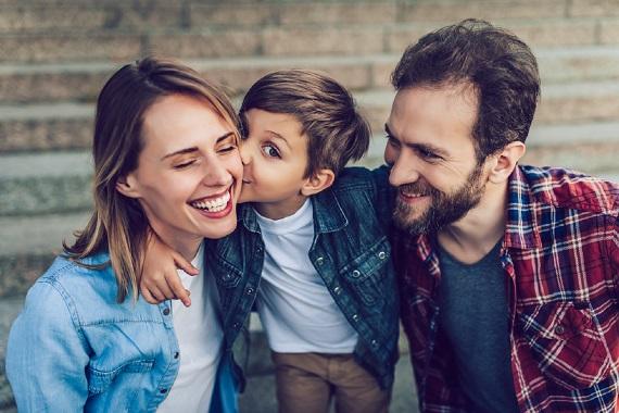 Familie fericita, copilul dandu-i un pupic mamei sale