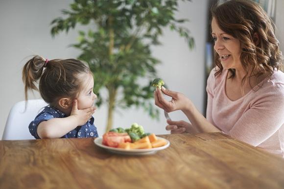 Mama ce incearca sa-si convinga fetita sa guste si broccoli