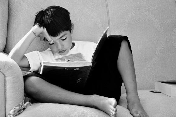 Baietel ce citeste pe canapea