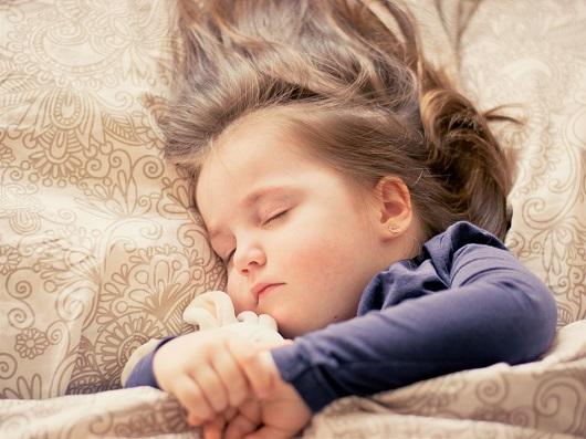 Fetita care doarme avand in brate o jucarie de plus
