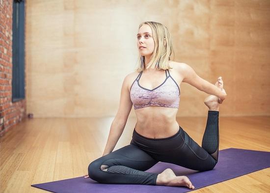 Femeie ce face un exercitiu in care se combina yoga si fitness-ul