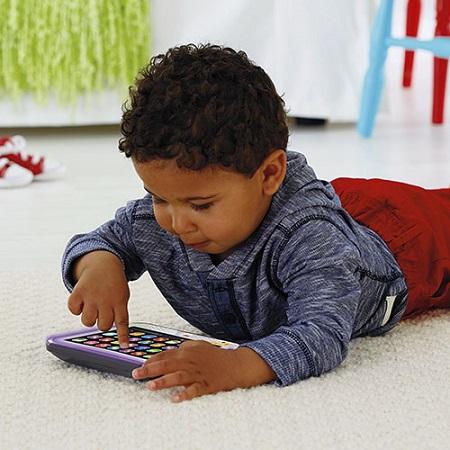 Baietel ce se joaca cu o tableta de jucarie