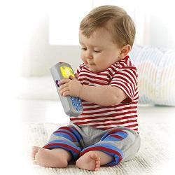 Bebelus ce se joaca cu o telecomanda de jucarie