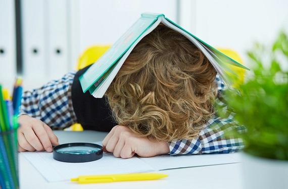 Copil ce a adormit pe birou, cu o carte pe cap si cu o lupa in mana