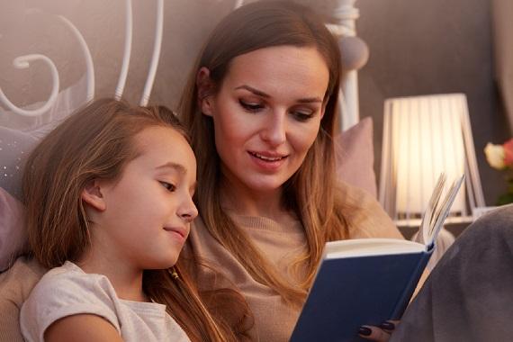 Fetita ce citeste alaturi de mama ei