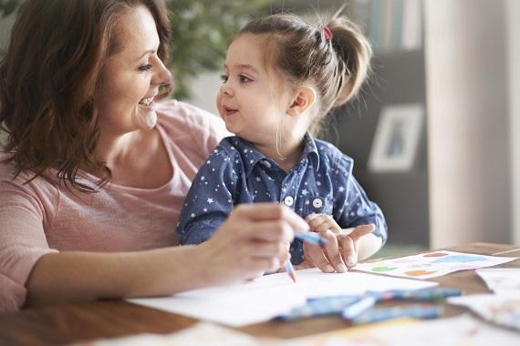 Fetita ce deseneaza alaturi de mama ei