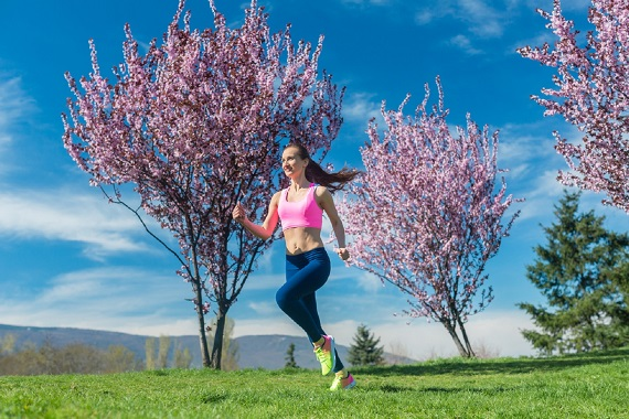 Femeie ce alearga in preajma unor copaci infloriti