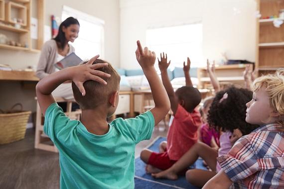 Copii la gradinita sau la scoala, care ridica mana