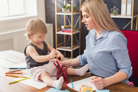 Mama ce sta pe langa fetita ei, care doreste sa incerce sa deseneze