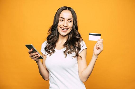 Femeie care tine intr-o mana un telefon și in cealalta un card