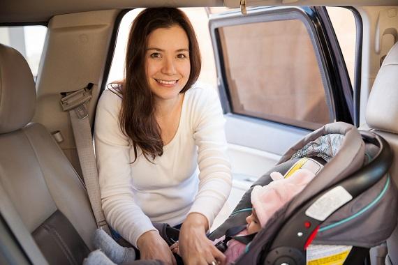 Mama care isi verifica bebelusul pus in scaunul auto