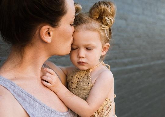 Mama ce isi saruta fiica pe frunte